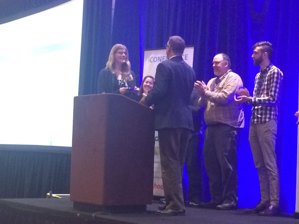 Alex Wade presenting the Lee Dirks Best Paper Award to Kathleen Pine during an awards ceremony at iConference 2016.