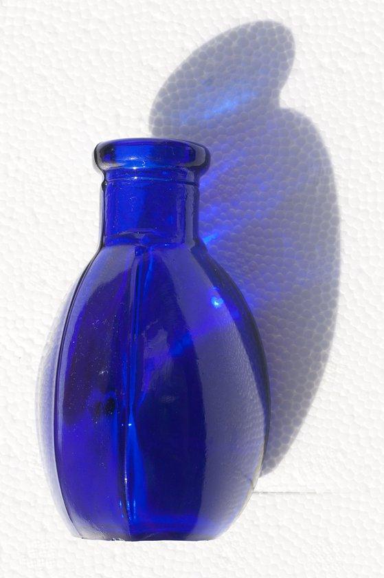 Triangular blue glass bottle